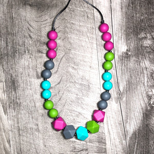 Teething necklace from chompy chic in bright rainbow colors with Tekhni woven delta cleo