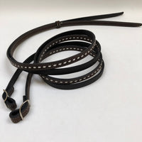 Dark brown handmade bridles and reins with buck stitch and white lace