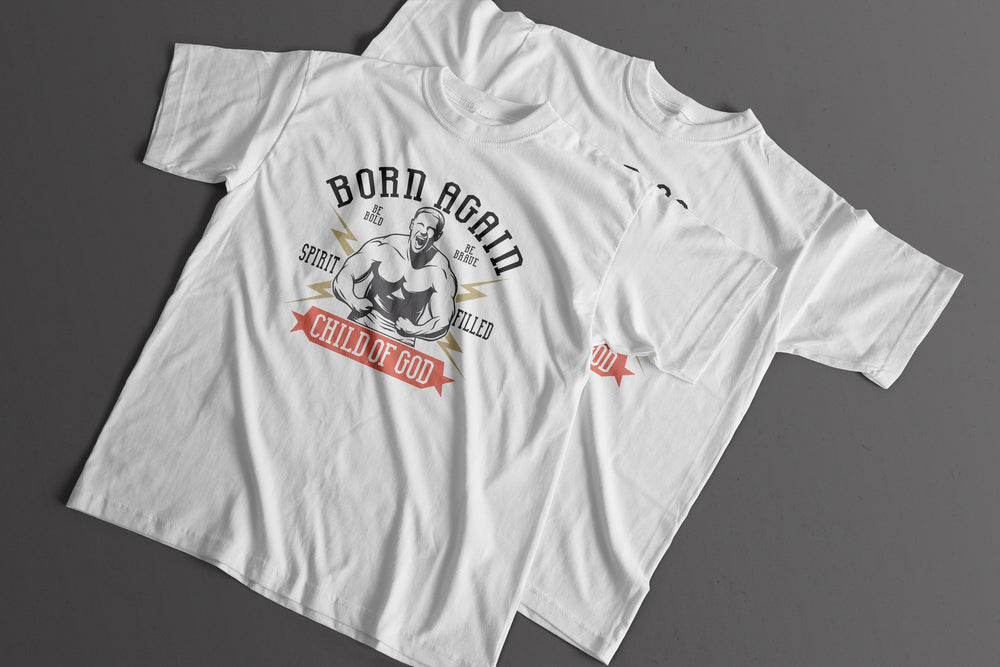 Two t-shirts overlapping one another laying on light grey background. The t-shirts have a graphic design on it which says born again spirit filled child of God, with a strongman character flexing his muscles gritting his face.