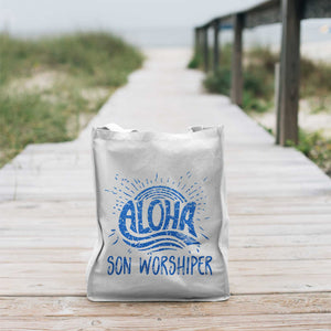 aloha son worshiper svg shown in blue glitter on a beach bag at the beach