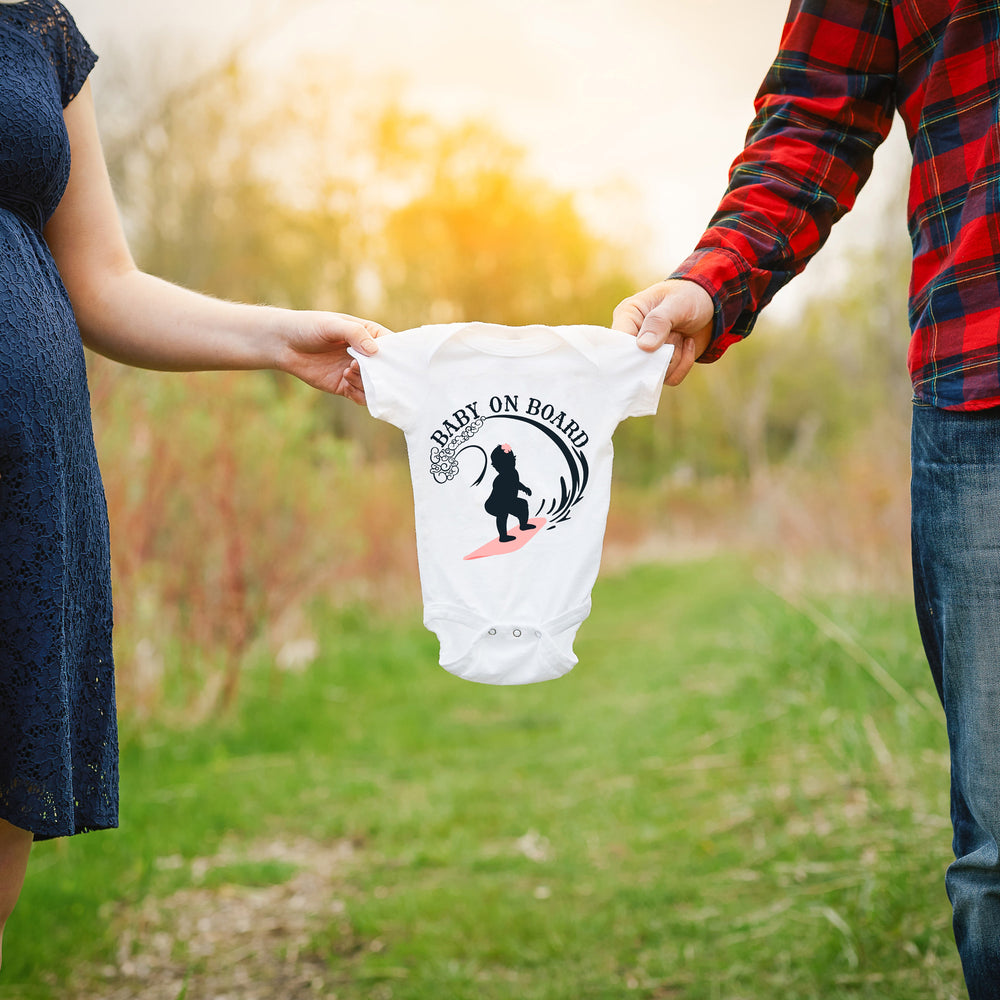 a couple holding a baby onesie between them, printed with Baby On Board - Surfing Girl svg as a pregnancy announcement