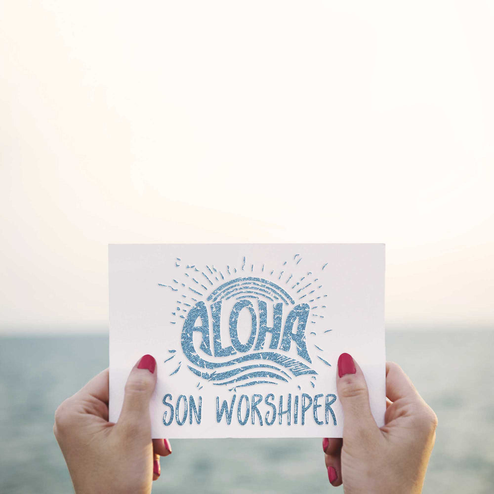 aloha son worshiper svg embossed on a card in blue glitter, held up in front of an ocean view