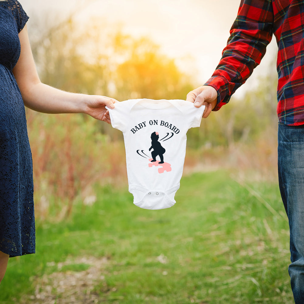 a couple holding a baby onesie between them, printed with Baby On Board - Skateboarding Girl SVG as a pregnancy announcement