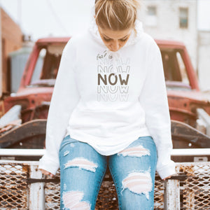a young woman sitting on a broken down car, wearing a hoodie printed with Faith Is Now - SVG