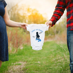 Load image into Gallery viewer, a couple holding up a onesie with baby on board - skateboarding boy svg printed in blue as a gender reveal announcement