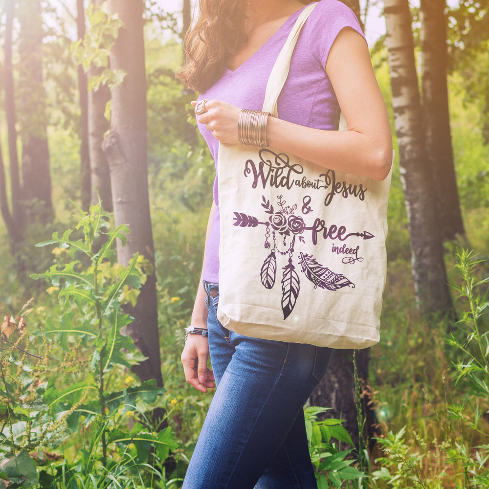 a woman outdoors carrying a bag printed with the free indeed svg in purple