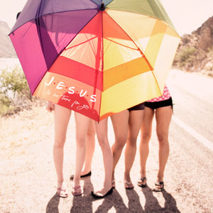 Load image into Gallery viewer, four young girls by a lake, hiding behind a colorful beach umbrella printed with Jesus, I'll be there for you svg in white