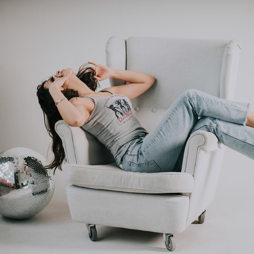 Load image into Gallery viewer, young woman enjoying music, laying across an armchair, wearing a tee with  when-in-doubt-dance-it-out-svg.