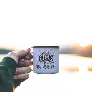 aloha son worshiper svg shown on a mug held in front of a morning lake scene