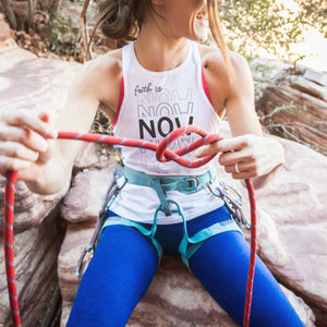 a happy young woman outdoors, geared up for climbing, wearing a tank printed with Faith Is Now - SVG