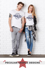 a beautiful young couple leaning against a wall, dressed casually, wearing the Healed shirt in white