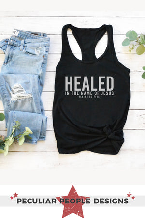 Load image into Gallery viewer, the ideal racerback tank layed out with jeans and greenery on a wood tabletop