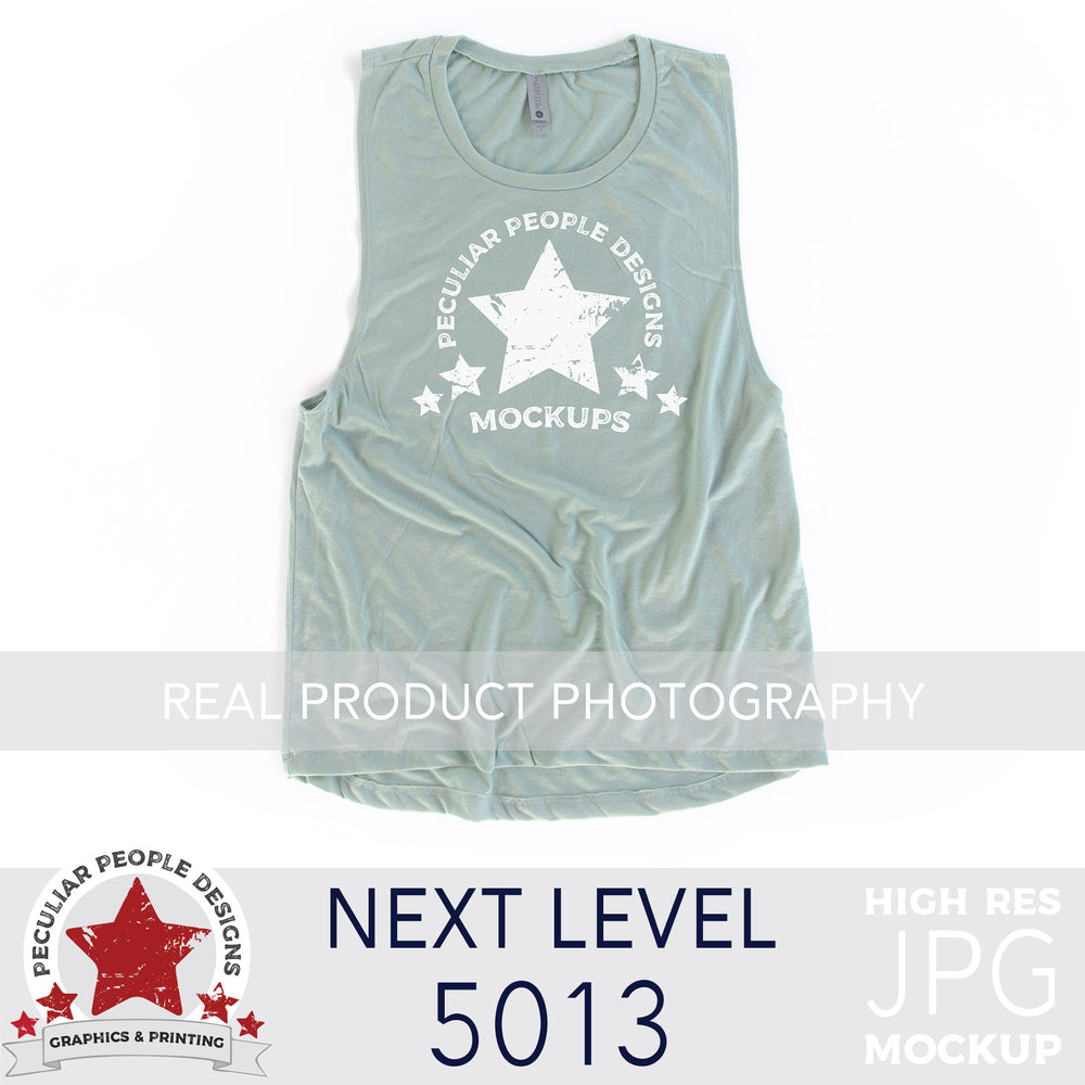 a Stonewash Green, next level 5013 muscle tank flat lay mockup with a white background by peculiar people designs