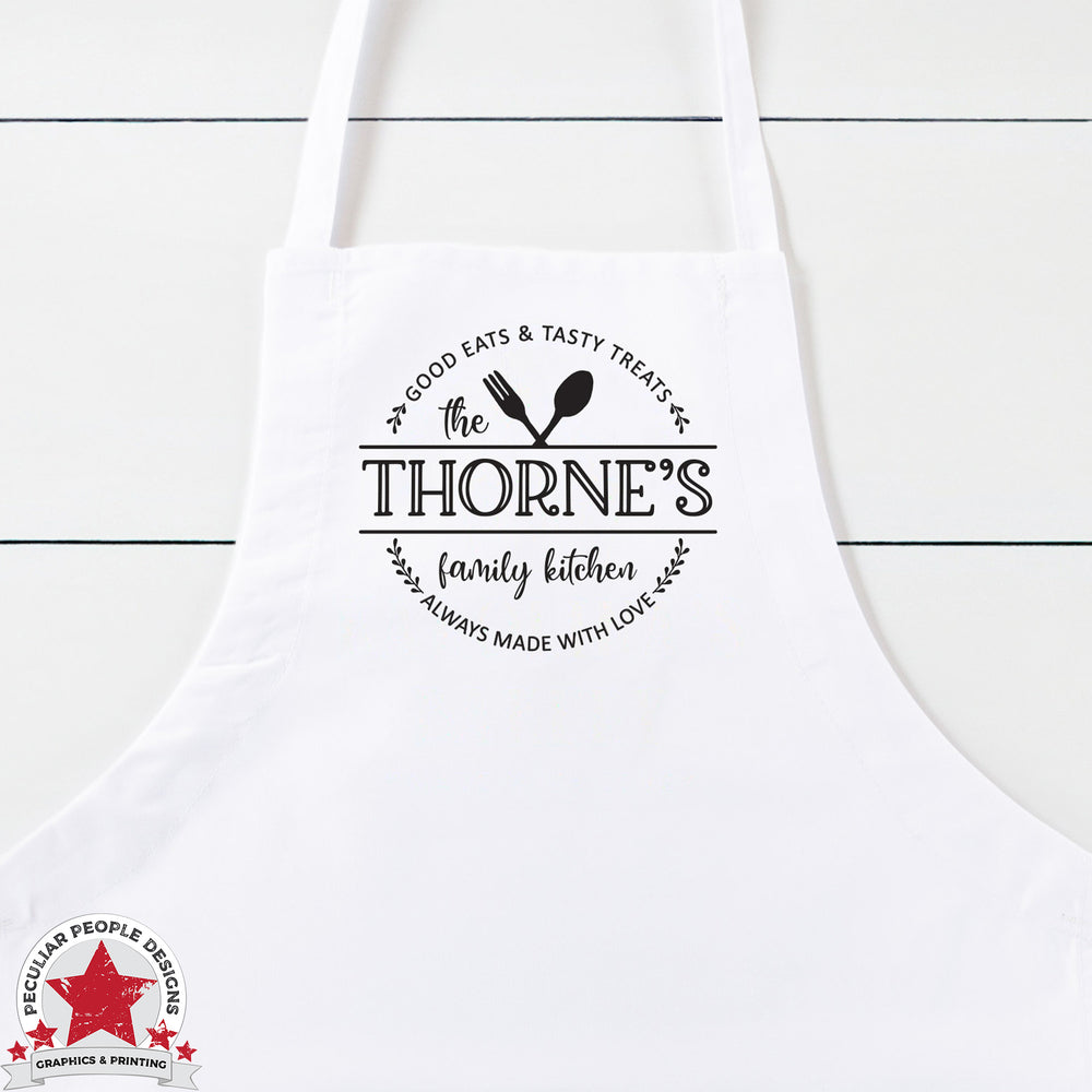 "a white kitchen apron printed with a graphic of crossed silverware in a round wreath with text reading ""the thorne's family kitchen. good eats & tasty treats, always make with love""."""