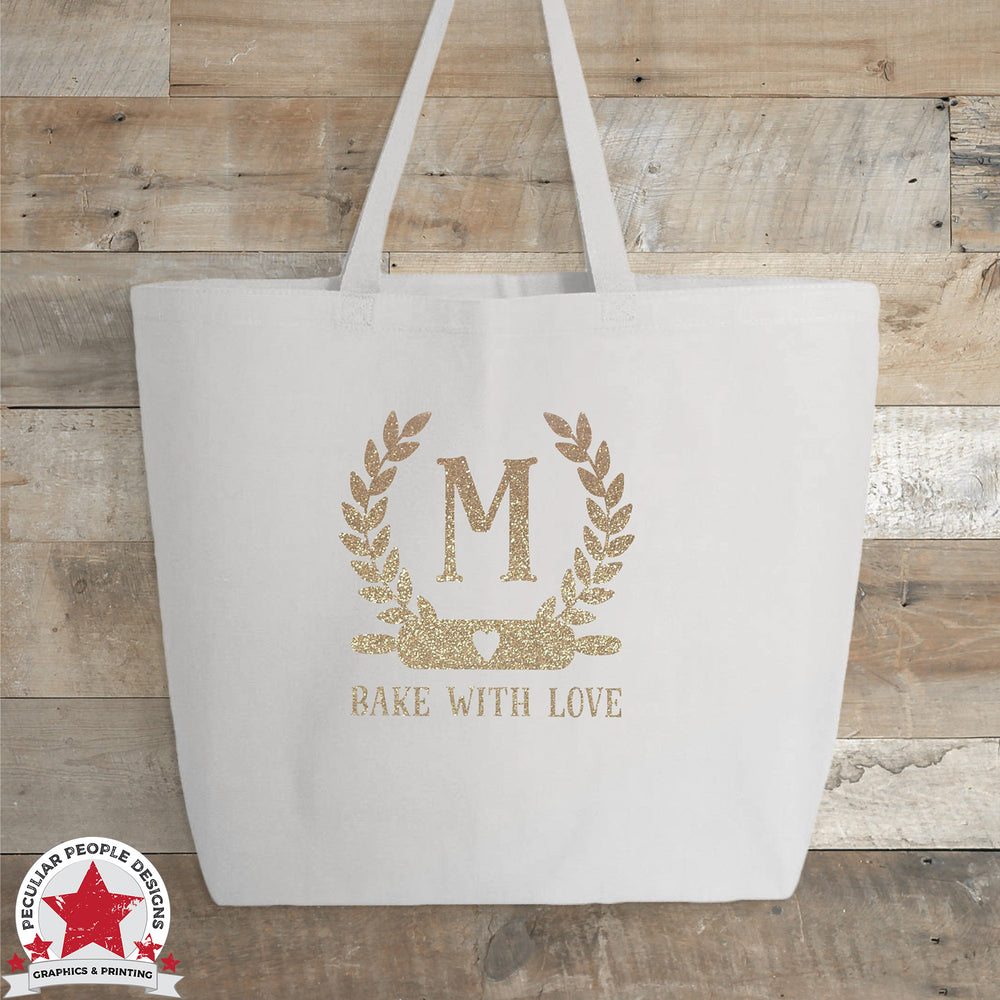 a white tote printed with a laurel wreath with a rolling pin on the bottom, framing a monogram letter. Under the wreath, text reads 'bake with love