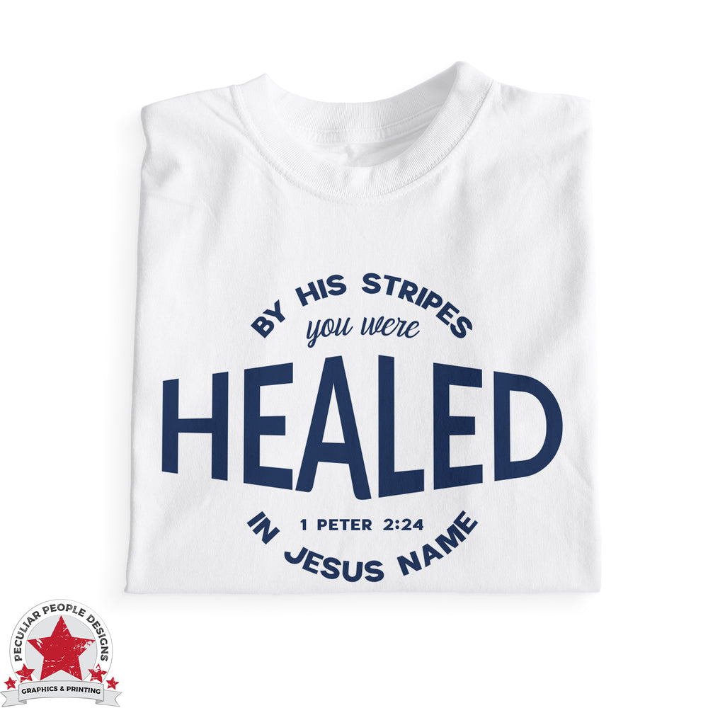 "a folded white tshirt with navy print, reading ""by his stripes you were healed in Jesus name, 1 Peter 2:24"""