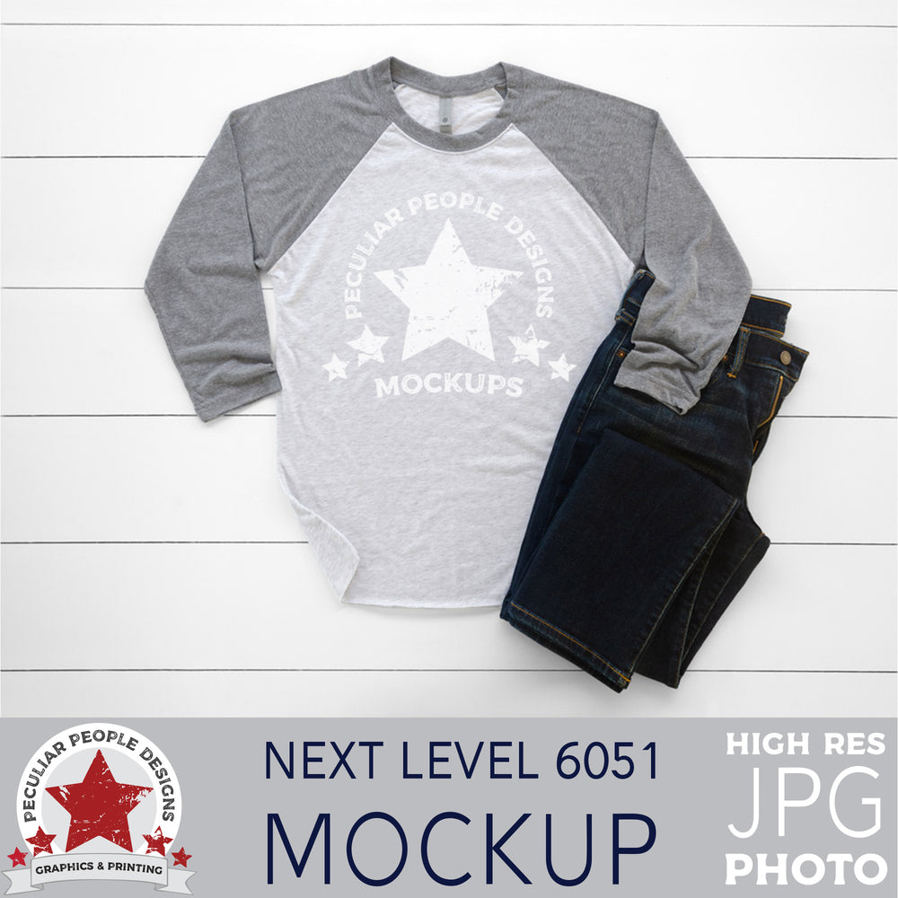 mock up photo of a grey raglan, layed out in a masculine way with men's jeans, on a wood background