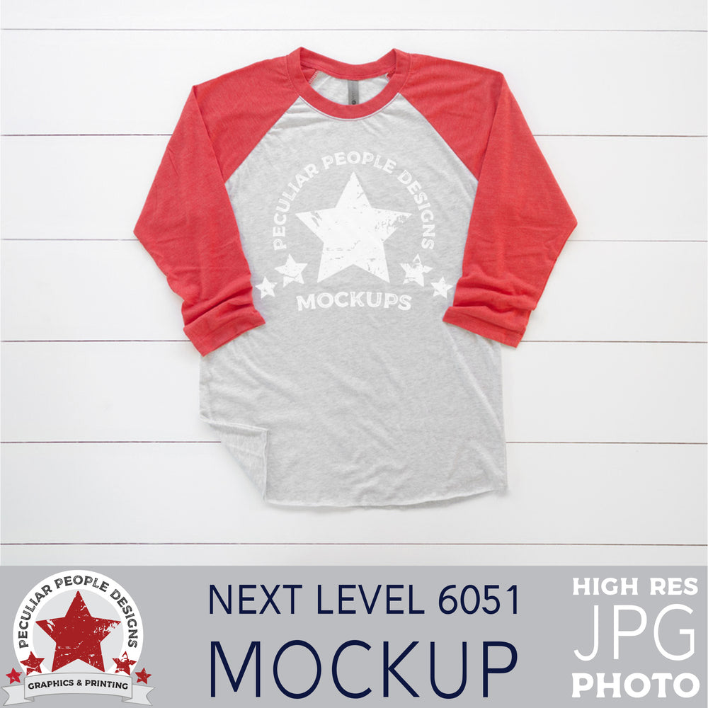 mock up photo of a red raglan, layed out in a masculine way, on a wood background