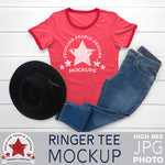 a mockup image of a red ringer tee, a black hat and blue jeans, layed out flat on a wood background