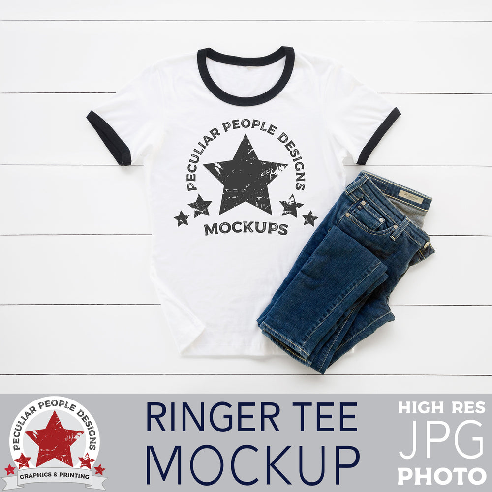 a mockup image of a black/white ringer tee and blue jeans, layed out flat on a wood background