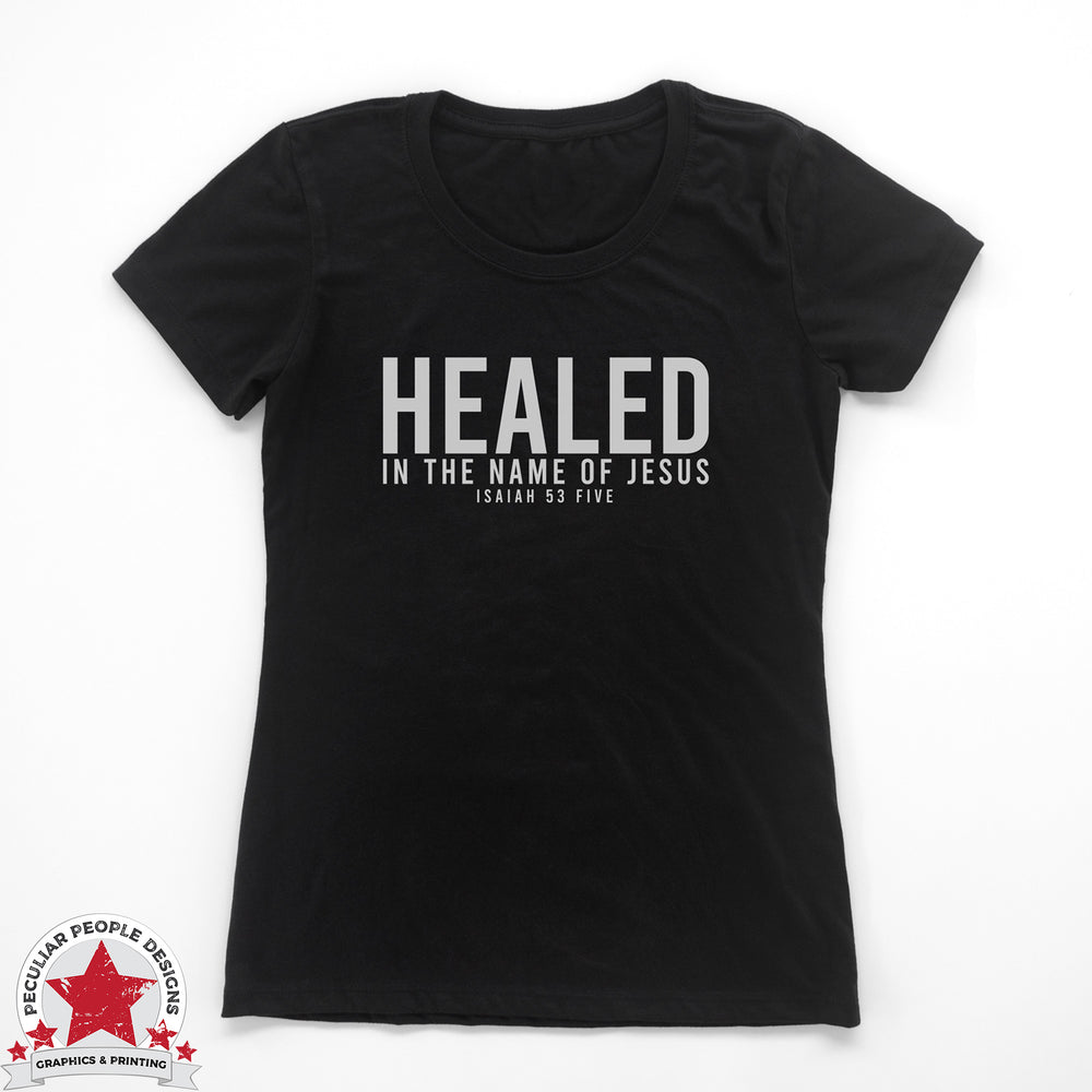 "A women's fit, loose crew neck tee in black with the text in white ""healed in the name of Jesus, Isaiah 53 five"""