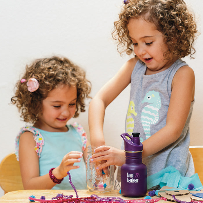 Two girls playing arts and crafts at table with Klean Kanteen Classic Sport water bottle