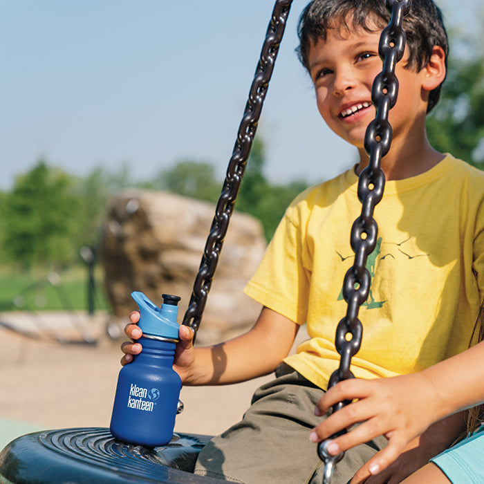 Boy sitting on swing smiling with Klean Kanteen Kid Classic sport bottle in hand