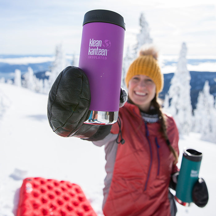 Woman holding Klean Kanteen TKWide up to camera on snowy mountain