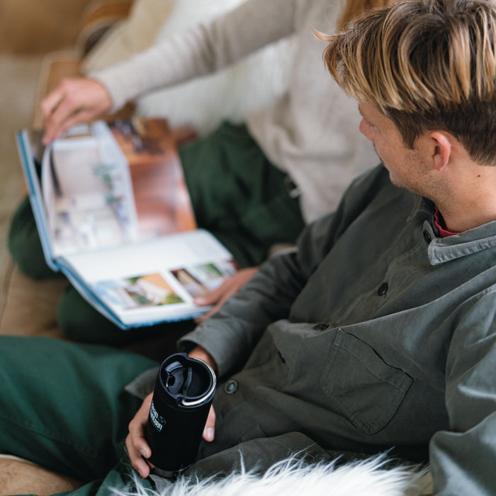 Man relaxing on couch holding Klean Kanteen TKWide drink bottle