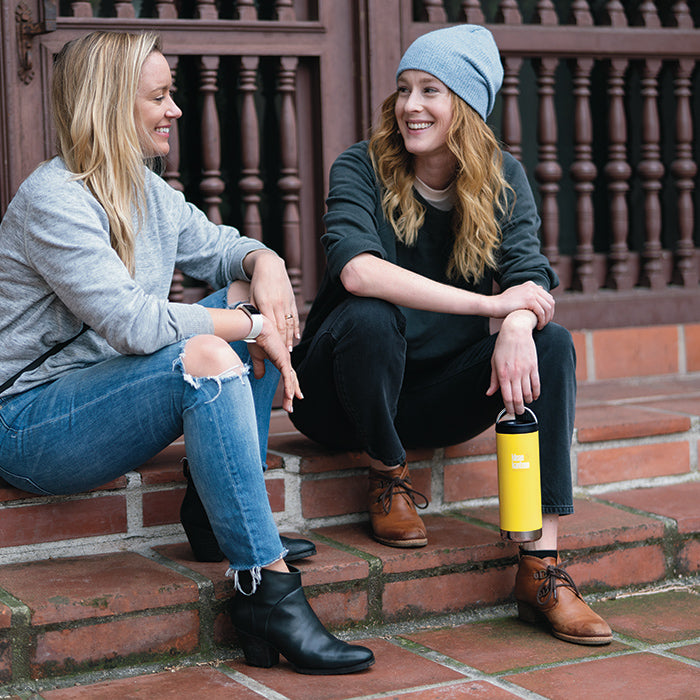 Women chatting sitting on steps holding Klean Kanteen TKWide insulated mugs