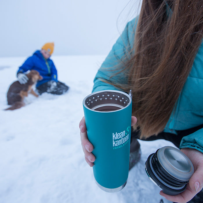 Woman crouched in snow holding Klean Kanteen TKWide insulated mug in one hand and lid in the other