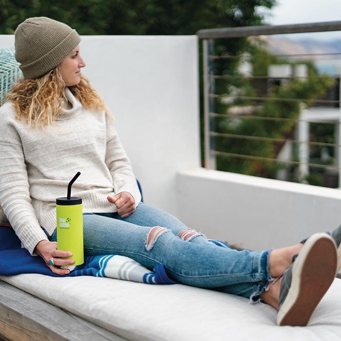 Woman relaxing on balcony chair holding Klean Kanteen TKWide insulated mug