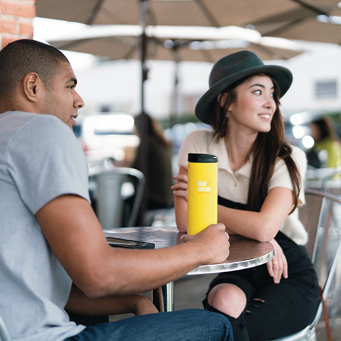 Man sitting at cafe holding Klean Kanteen TKWide insulated mug