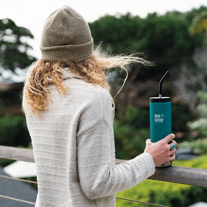 Woman standing on balcony holding Klean Kanteen TKWide insulated bottle with straw cap