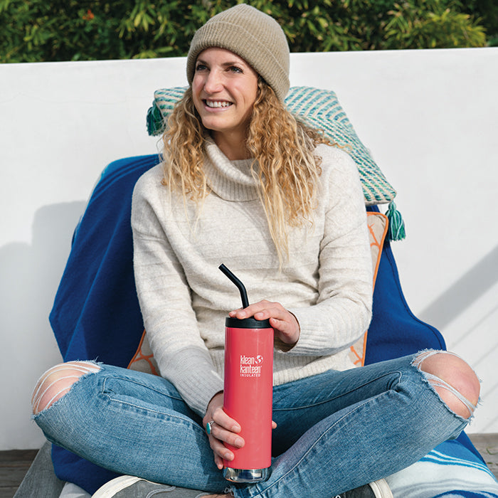 Woman sitting crossed legged on balcony chair holding Klean Kanteen TKWide insulated mug