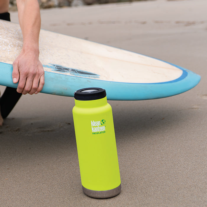 Klean Kanteen TKWide insulated bottle with loop cap standing up in sand at beach