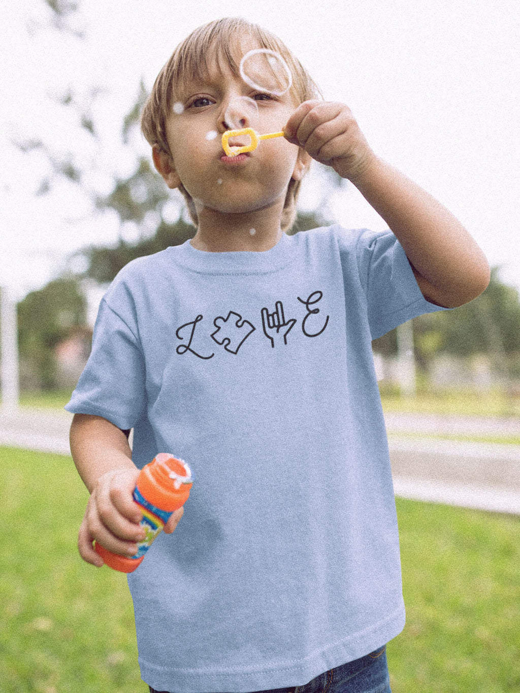 Boy Blowing Bubbles Wearing Love Autism T-Shirt