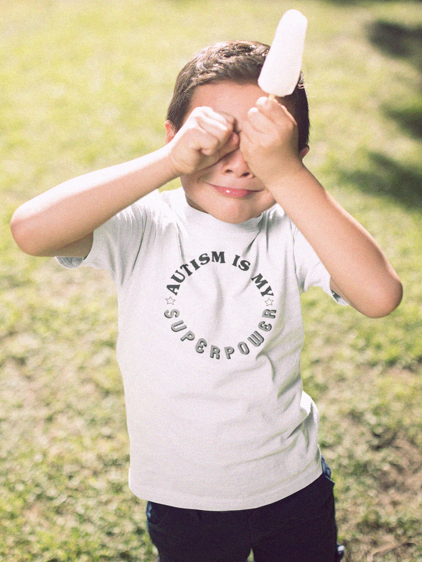 boy wearing autism is my superpower t-shirt covering eyes