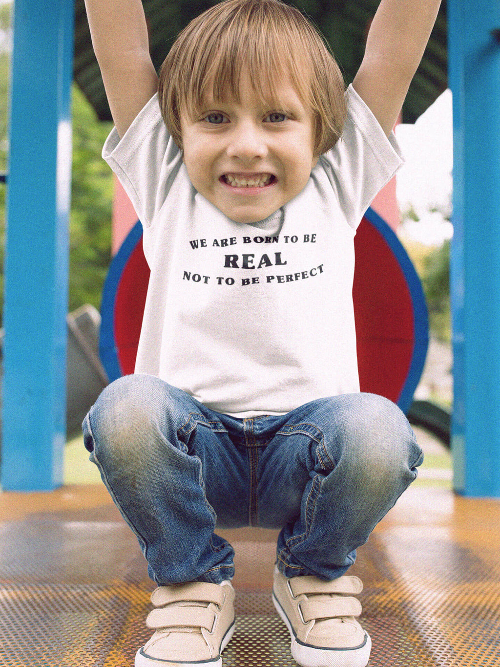 boy wearing born to be real t-shirt on playground