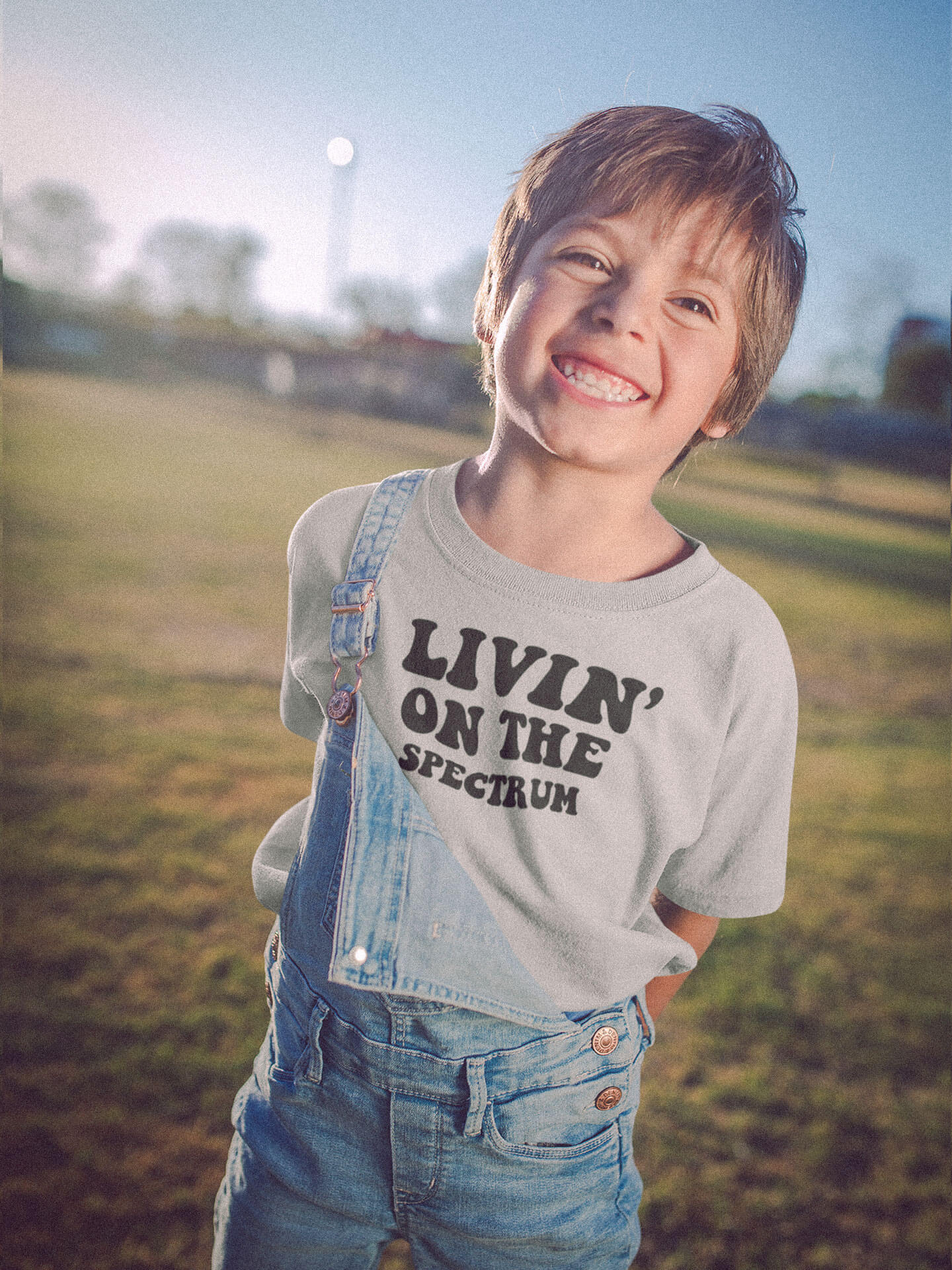 boy wearing livin on the spectrum autism grey t-shirt in field smiling