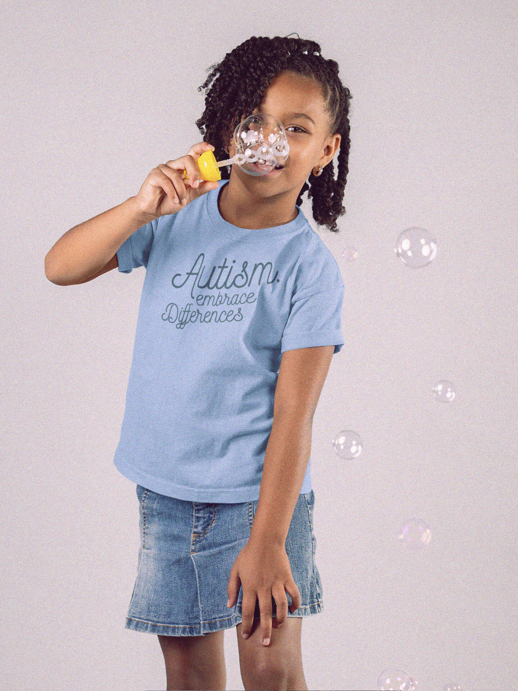 girl blowing bubbles wearing autism embrace differences t-shirt
