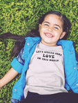 girl laying in grass with lets spread some love t-shirt