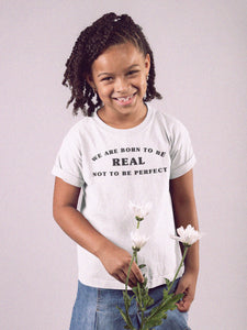 girl wearing born to be real t-shirt with flowers