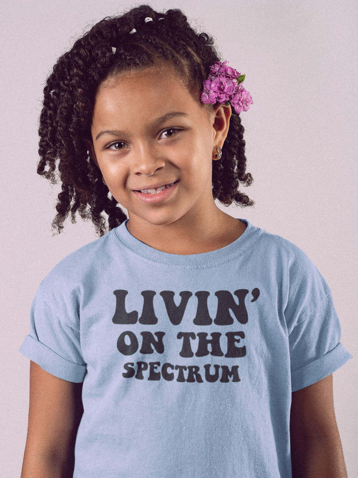 girl wearing livin on the spectrum autism blue t-shirt smiling