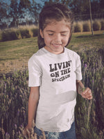 Girl Wearing Livin On The Spectrum Autism T-Shirt In Field