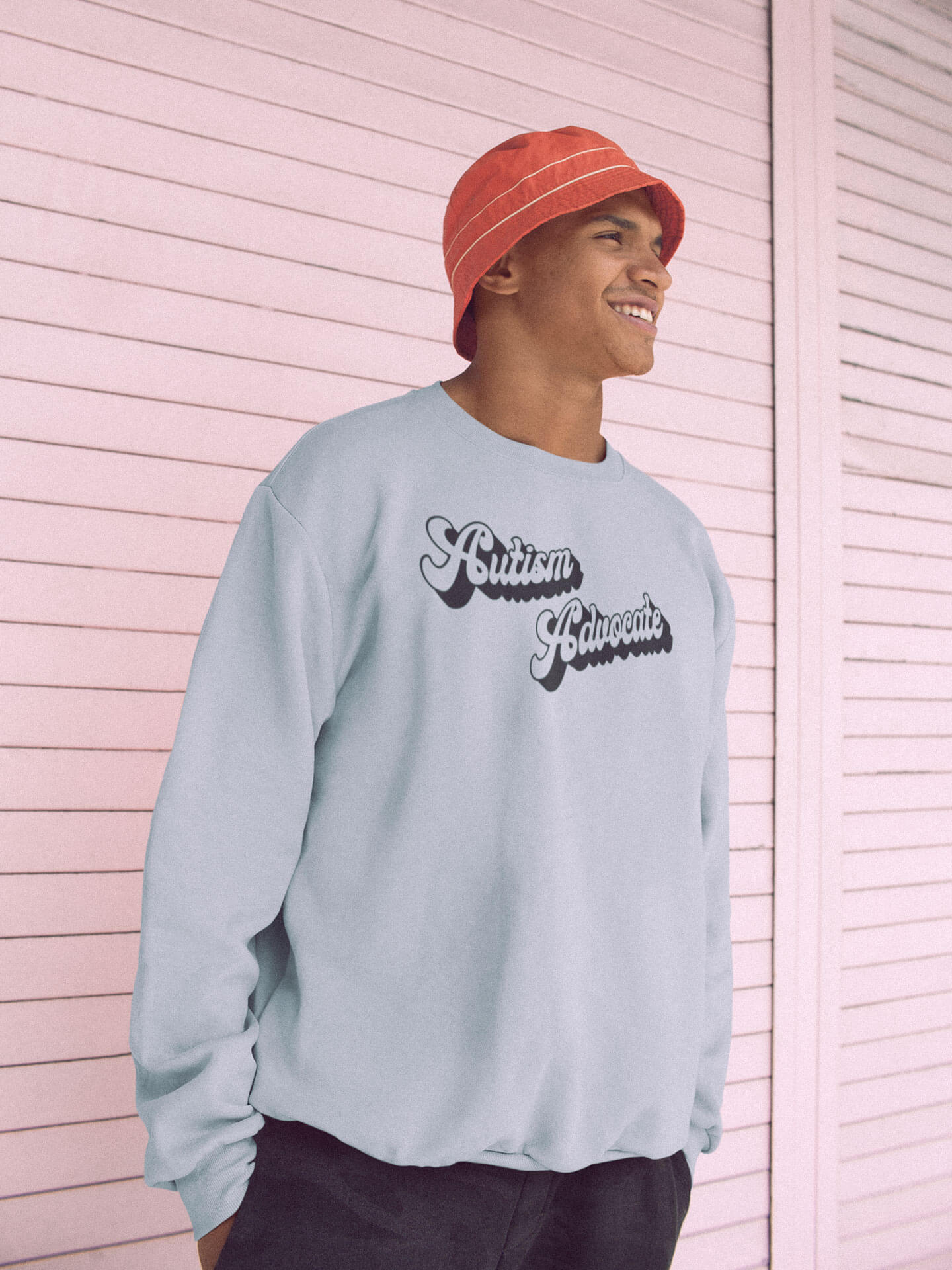 happy man wearing autism advocate sweatshirt standing against a pink metal wall