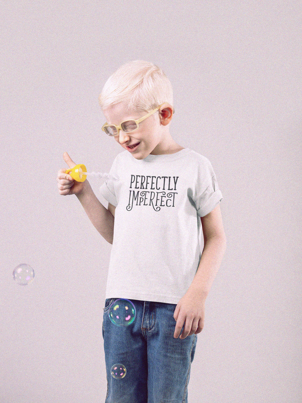 kid blowing bubbles wearing perfectly imperfect t-shirt