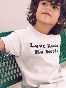 kid sitting on park bench wearing love needs no words t-shirt