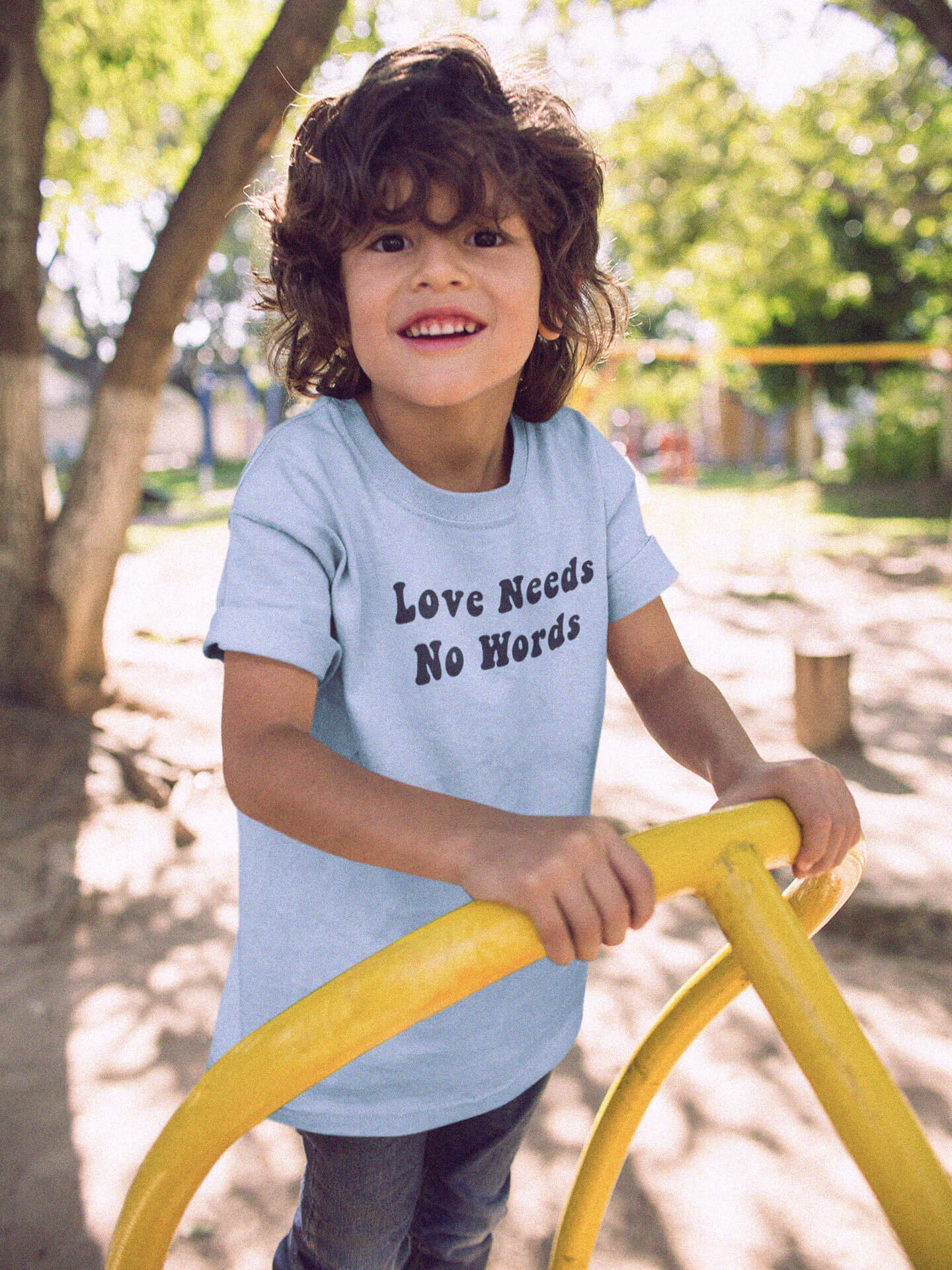 kid smiling wearing love needs no words t-shirt on playground