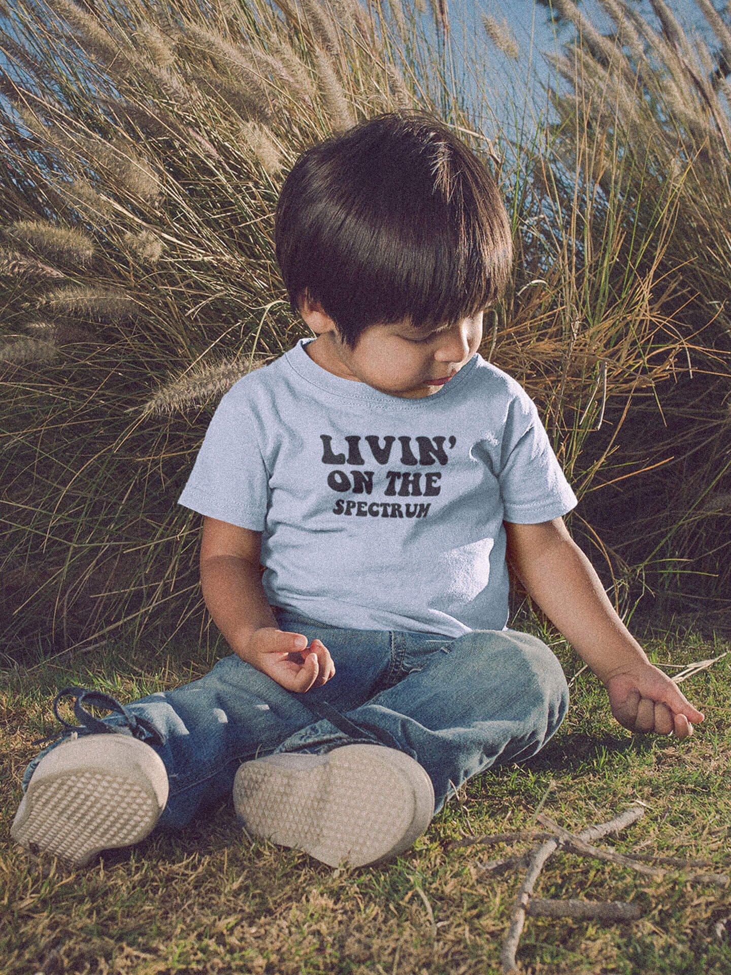 Kid Wearing Blue Livin On The Spectrum T-Shirt Sitting Down